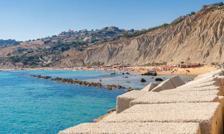 High rocky cliffs and the promontory frame the blue sea and the sandy beach at Licata, Sicily