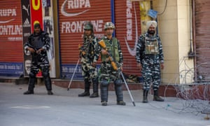 Indian paramilitary troopers stand guard in front of shuttered shops in a deserted square in Srinagar.
