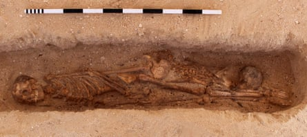 A multiple burial from the North Tombs Cemetery, Amarna, Egypt. Two skeletons laid one on top of the other in a single grave with their heads at opposite ends.