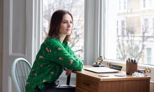 Elizabeth Day sitting at a desk looking out of the window