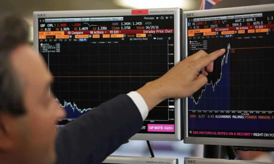 A man points to a steep rise in a financial index on a  computer screen
