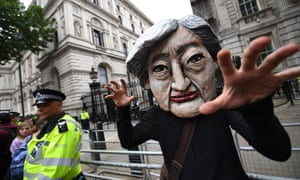 An anti-austerity protester in a Theresa May mask outside Downing Street during the 'Not One Day More' march in July 2017.