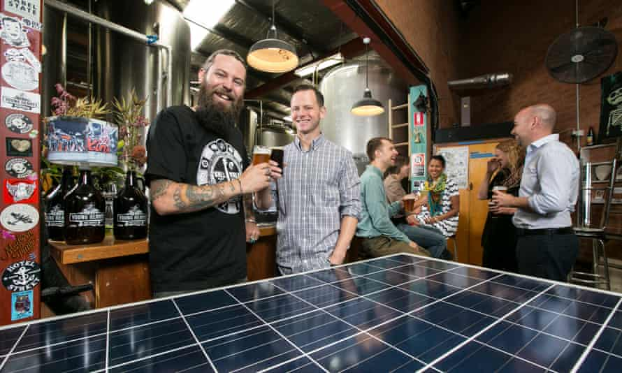 Oscar McMahon of Young Henrys and Jake Steele of Solargain pose at the Young Henrys brewery with one of the solar panels to be installed as part of a community solar project.