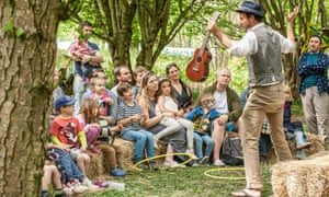Kids and parents watch an entertainer at the Elderflower Fields festival in East Sussex, UK.