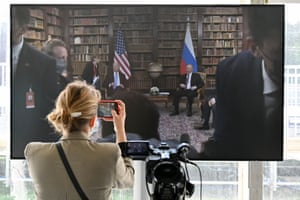 A journalist takes a picture of the screen displayed in the press room