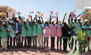 Children in Dakar wave national flags as they greet Macky Sall and Emmanuel Macron,