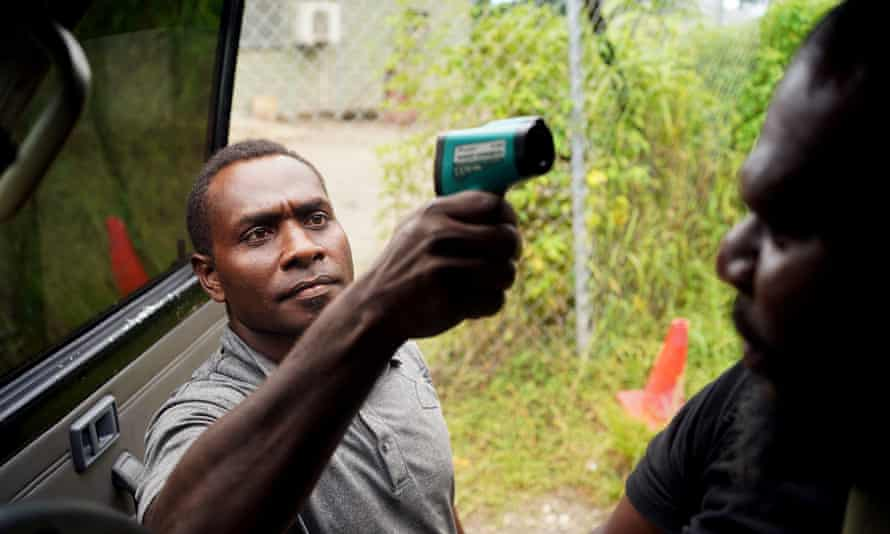 A guard from a logging mill in East New Britain province in Papua New Guinea, checks the temperature of police and passengers in the vehicle before they are allowed to enter the compound.