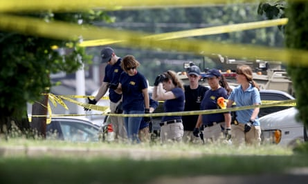 Investigators from the FBI look for evidence in a parking lot next to Eugene Simpson Field, where a gunman opened fire.