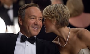 Kevin Spacey, as Frank Underwood, smiles as Robin Wright, playing his wife Claire, whispers in his ear, in House of Cards