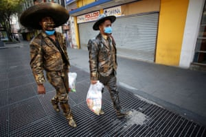 Mexico City, Mexico Street performers dressed as statues carry food donated by an organisation to help them due to the lack of work