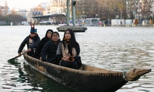 Members of the Sarayaku indigenous community ride the 'Canoe of Life' along the Bassin de la Villette in Paris