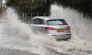A car drives through a flooded street in Whitley Bay, Tyne and Wear.
