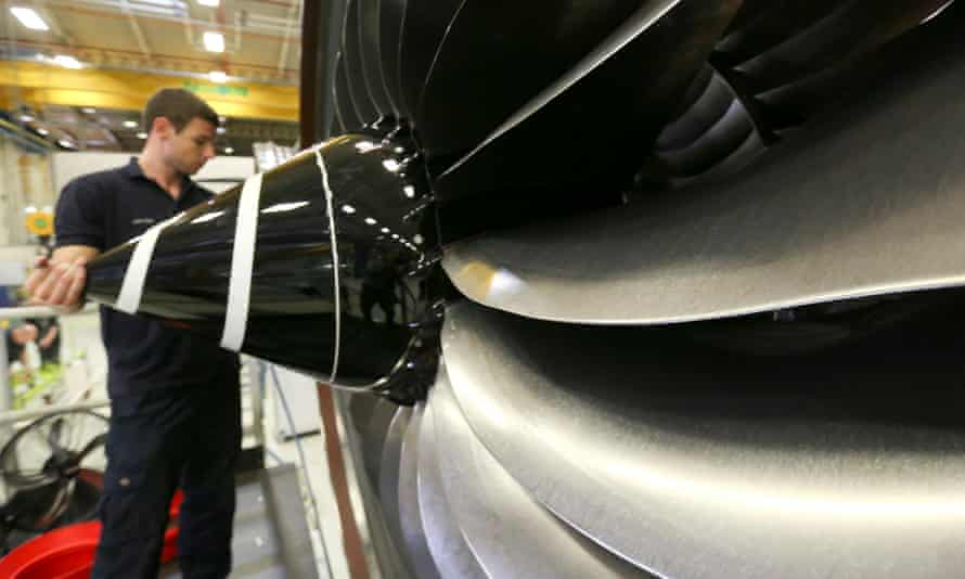 An employee checks the nose cone of a Trent XWB aircraft engine at the Rolls-Royce factory in Derby.