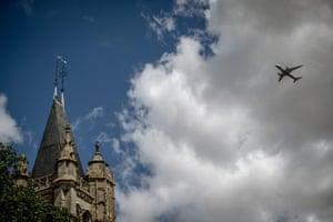 A plane flies over the Church of Saint-Pierre-Saint-Paul in Goussainville