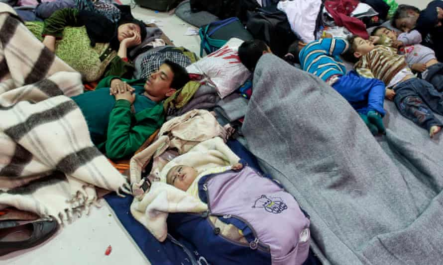 Migrants rest in the passenger terminal after arriving from the islands at the port of Piraeus.