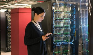 Server room technician works on digital tablet as she stands in a colorful brightly lit server room