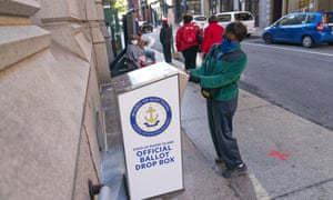 Eva Abodoadji drops off a mail ballot into an official ballot drop box in Providence, Rhode Island, on 14 October.
