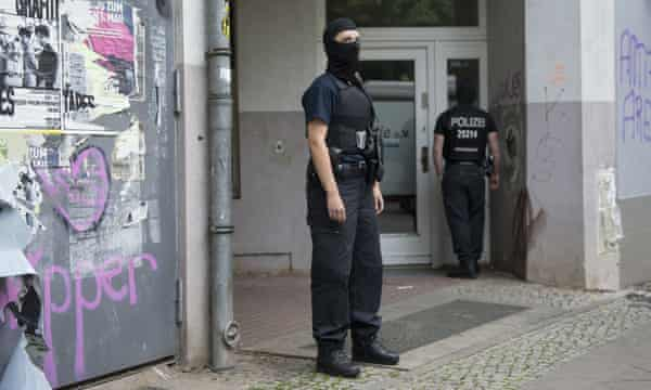 Masked police guard a house in Berlin on Wednesday after raids on several properties in connection with the gold coin heist.