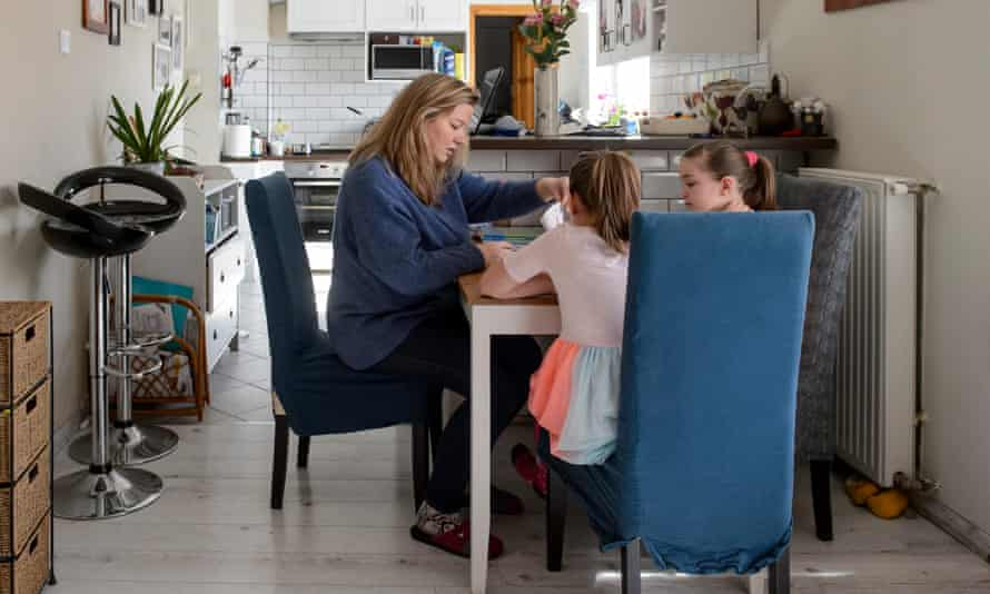 A woman helps her twin daughters to do their homework