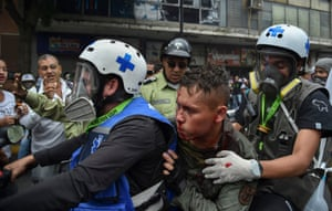Paramedics rescue a wounded member of the Bolivarian National Guard