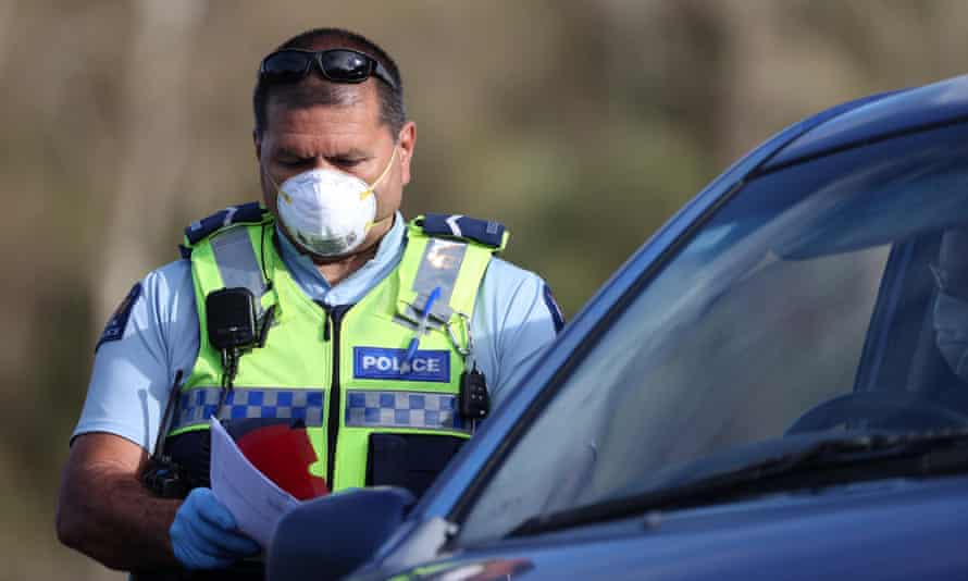 A masked police officer stands next to a car with papers in his hand