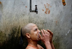 A priest takes a holy bath as part of a cleaning ritual