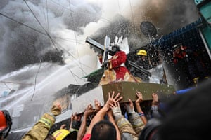Manila, Philippines: Residents and firefighters carry a Black Nazarene statue from a burning house after a fire hit an informal settlement.