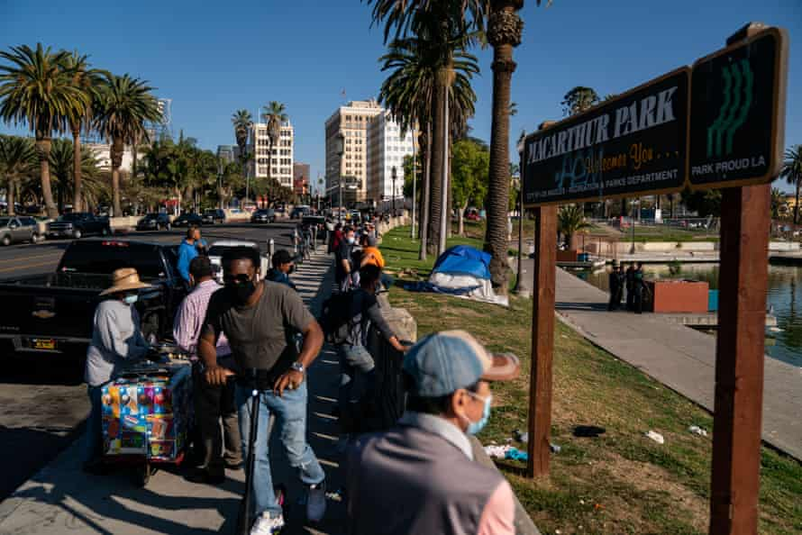 People gather to watch police activity at MacArthur Park in Los Angeles on 2 April.