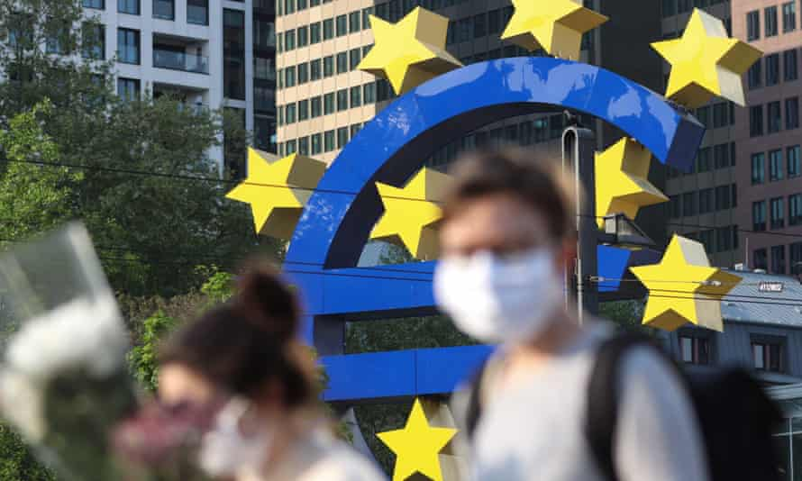 People wearing face masks pass a big euro sign in Frankfurt am Main, by the European Central Bank HQ.