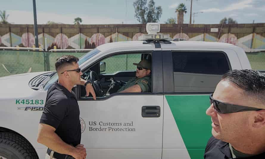 Border patrol agents gather along the border fence in Calexico, California.