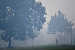 A woman walks through heavy smoke in Carrbrook