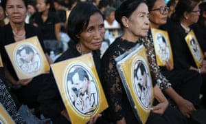Thai mourners in black hold portrait photos of the late King Bhumibol Adulyadej in Bangkok.