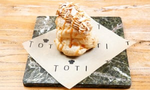 A tall choux bun with a caramel cream topping and caramel drizzle, all on a 'plate' of black marble