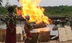 Women dry tapioca alongside gas flare in Nigeria