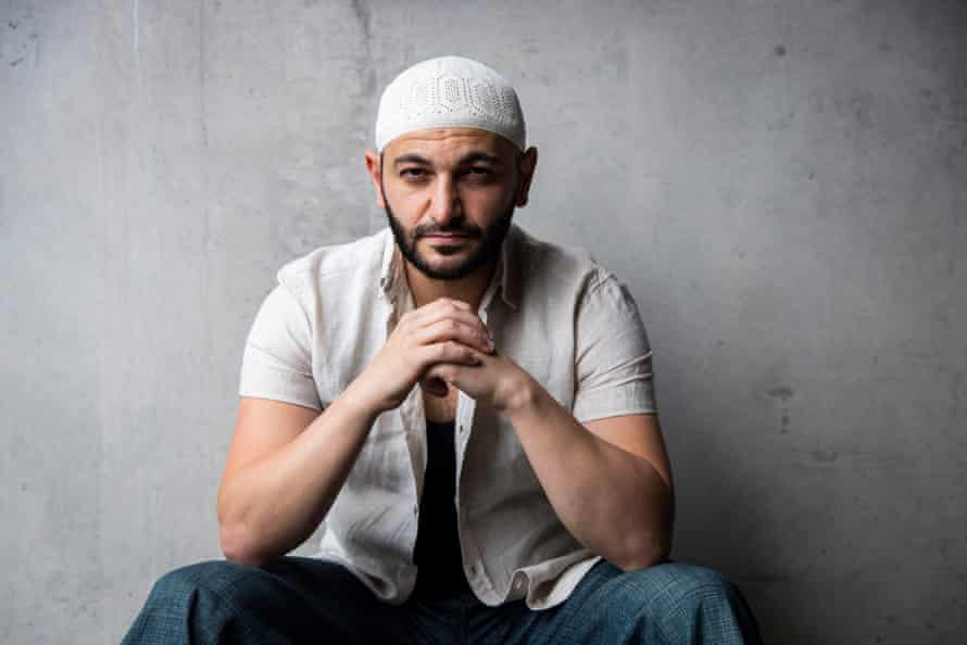 Arab-Australian author Michael Mohammed Ahmad rests elbows on his knees and looks at the camera
