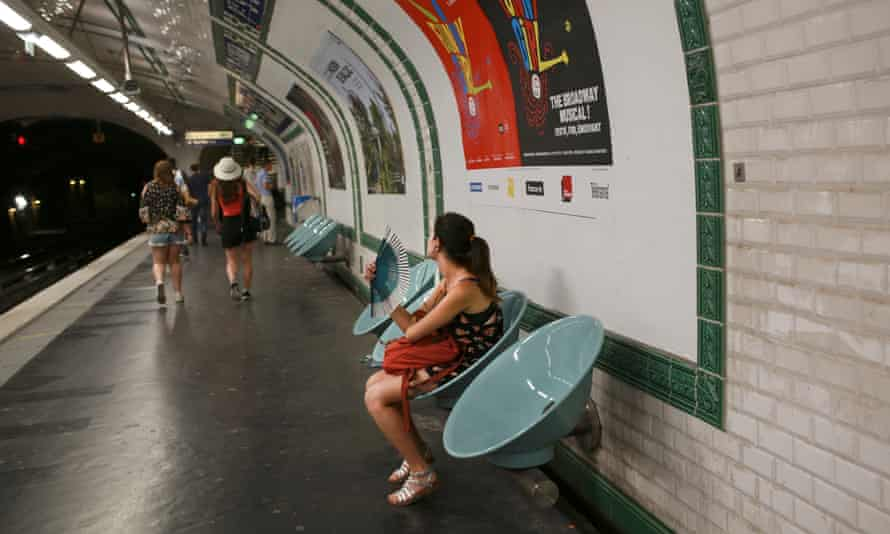 A woman fans herself inside a metro station in Paris as temperatures rise