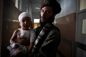 Aminullah holds his three year old son who is being treated at Mirwais Hospital for shrapnel wounds after a mine exploded near him.