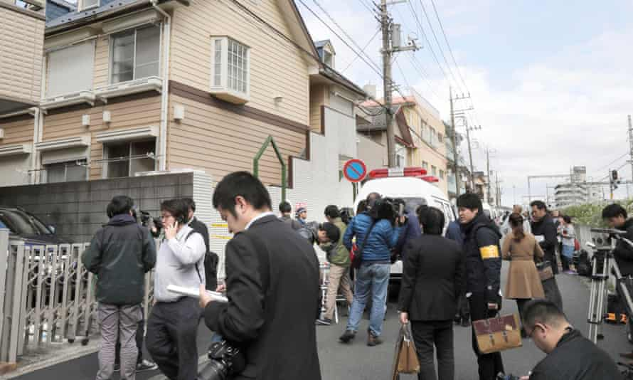 Members of the media gather in front of an apartment building where media reported nine bodies were found in Zama, Japan.