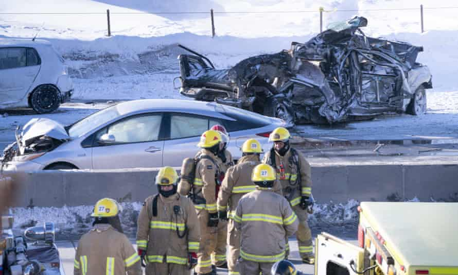 Emergency personnel stand next to demolished cars following a massive pileup involving numerous vehicles on the south shore of Montreal in La Prairie, Quebec.