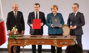 Merkel and Macron, centre, and their respective foreign ministers, pose with their signed treaty on Tuesday.