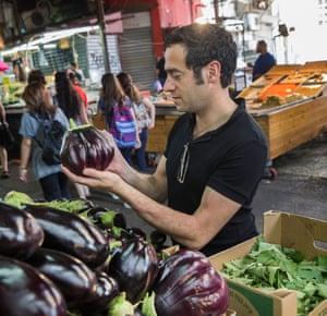 Jigal Krant selecting an eggplant