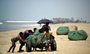 Rohingya refugees push fishing nets along the beach on Shamlapur beach