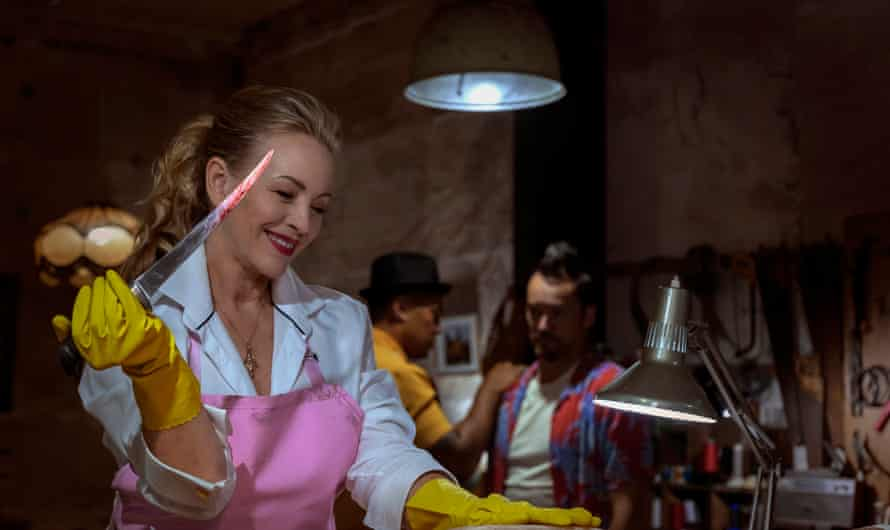 a blonde woman in a pink apron holding a blood-covered knife