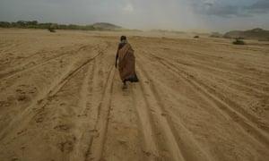 A woman walks across a dry riverbed in Kenya