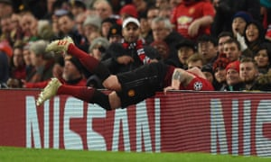 Manchester United's English defender Phil Jones trips over the advertising boards.