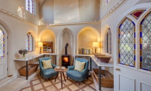 Lounge chairs with woodburning stove in a room at Cobham Dairy, Kent, UK.
