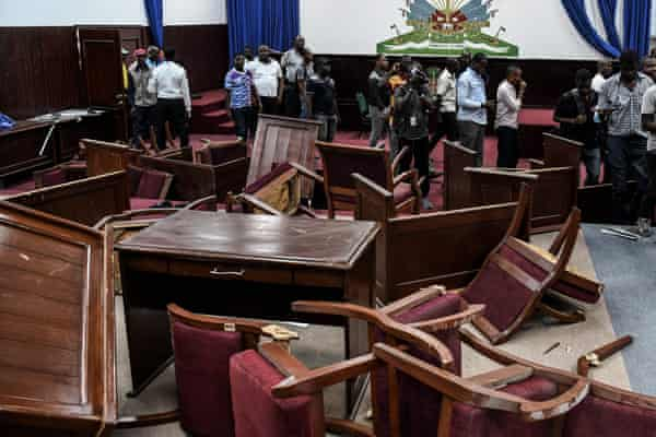 Officials and reporters beside broken furniture in Haiti's parliament after it was vandalised by opposition MPs in 2019.