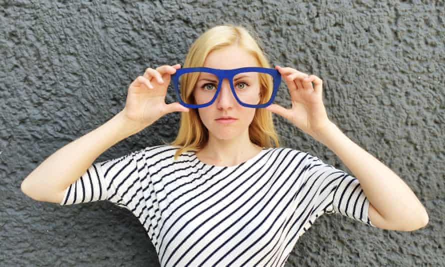 Young blonde woman wearing large blue novelty glasses
