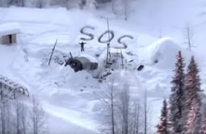 """Susitna valley, US In this image made from video released by Alaska state troopers, a man waves by an """"SOS"""" distress signal outside Susitna valley in Alaska. Troopers have rescued Tyson Steele, 30, who survived in a makeshift shelter after his remote cabin burned last month"""