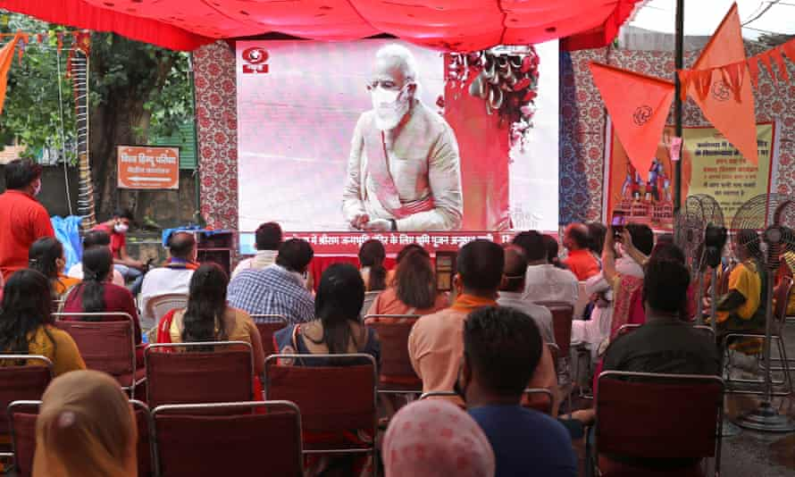 People watch the ceremony on a big screen in Delhi